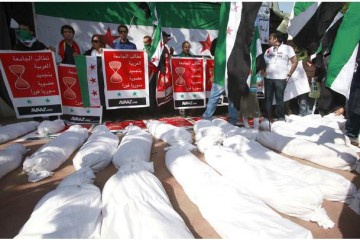 Burial shrouds, symbolizing bodies of the protesters who were killed during protests in Syria, are seen at an anti-Syrian government protest in Cairo
