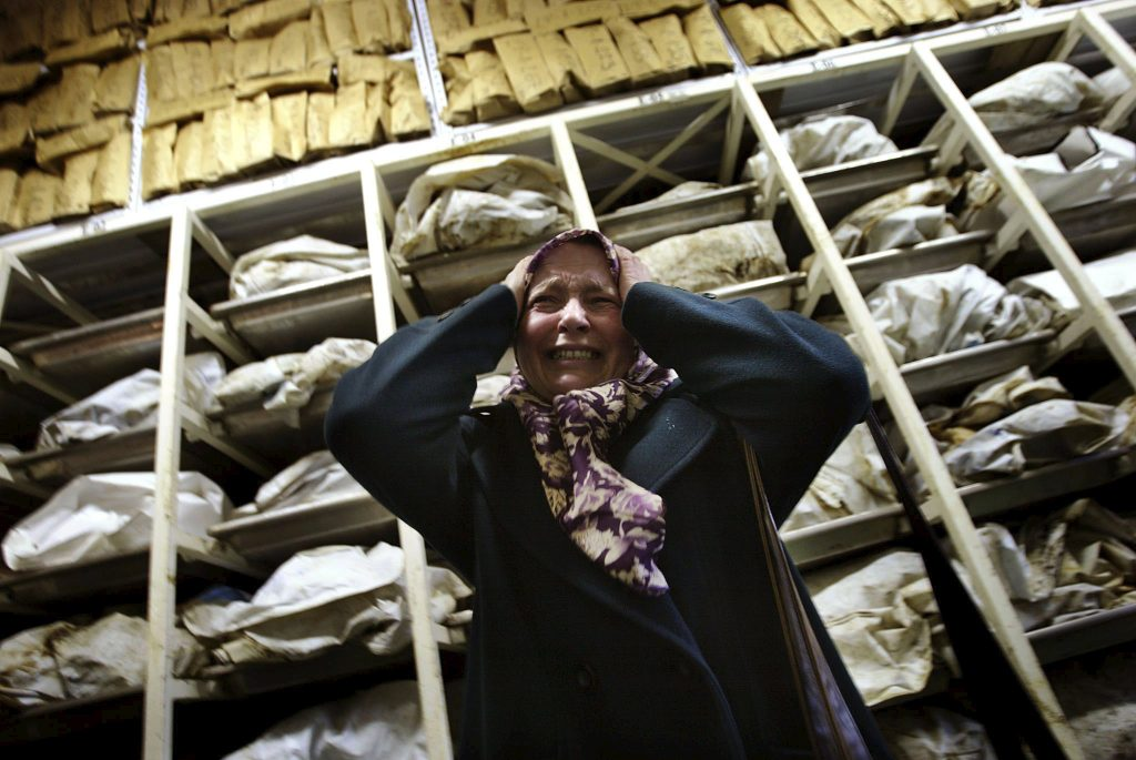 """Aida Civic, a Bosnian Muslim refugee woman from Srebrenica, screams as she enters a container with the remains of around 3,500 killed Bosnian Muslims, most of them from Srebrenica, in an identification centre of the Institute for missing persons in Tuzla in this December 10, 2002 file photo. Twenty years ago on July 11, 1995, towards the end of Bosnia's 1992-95 war, Bosnian Serb forces swept into the eastern Srebrenica enclave, a U.N.-designated """"safe haven"""". There they took 8,000 Muslim men and boys and executed them in the days that followed, dumping their bodies into pits in the surrounding forests.     REUTERS/Damir Sagolj/Files  TPX IMAGES OF THE DAY FROM THE FILES PACKAGE """"SREBRENICA MASSACRE - 20TH ANNIVERSARY� SEARCH """"SREBRENICA MASSACRE� FOR ALL 15 IMAGES      TPX IMAGES OF THE DAY"""