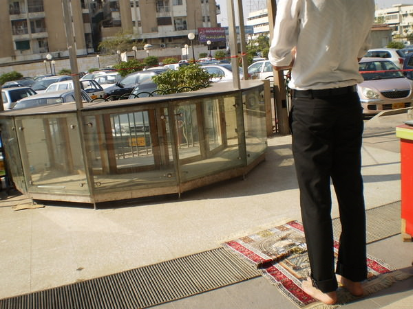 Sadaf: Young man offering dhuhr salah outside a shopping mall. The whole world is a prayer place for Muslims.